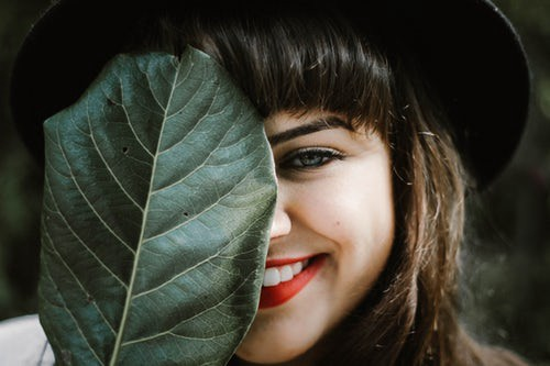Girl smiling behind a leaf